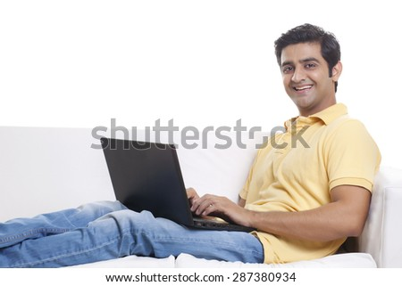 Portrait of handsome young man on sofa using laptop