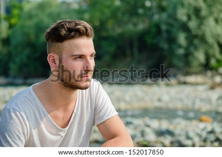 Portrait of handsome young man outdoors in nature, looking to a side - stock photo