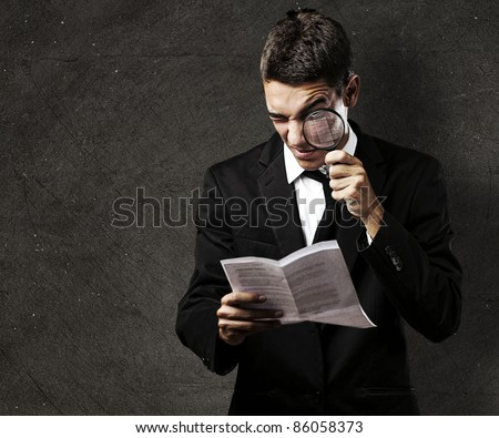 portrait of handsome young man reading a contract through a magnifying glass against a grunge background - stock photo