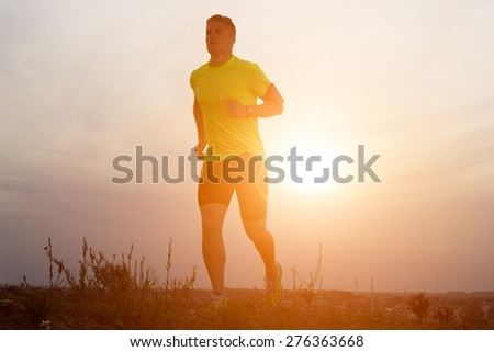 Portrait of handsome young man running in the park. - stock photo