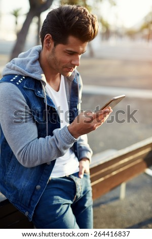 Portrait of handsome young man sending a text message while standing outside, male student reading text messages outdoors, stylish brunette hipster using cell phone at sunny evening, flare sunshine
