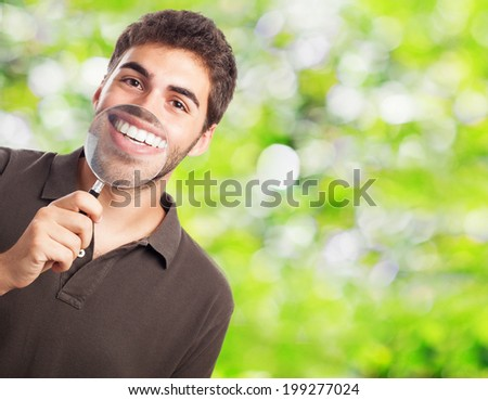 portrait of handsome young man showing his teeth trough a magnifying glass - stock photo