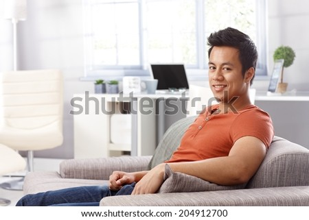 Portrait of handsome young man sitting at home on sofa, smiling, looking at camera. - stock photo