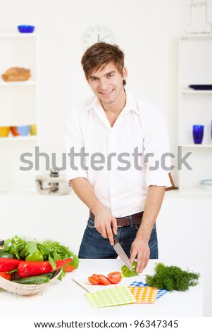 portrait of handsome young man slice, cutting green pepper, tomato in the kitchen, cooking, prepare  vegetable salad, happy smile, looking at camera