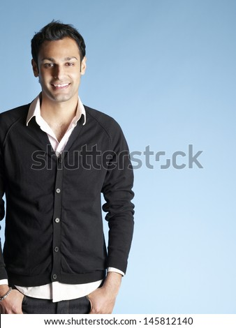 Portrait of handsome young man smiling isolated on blue background
