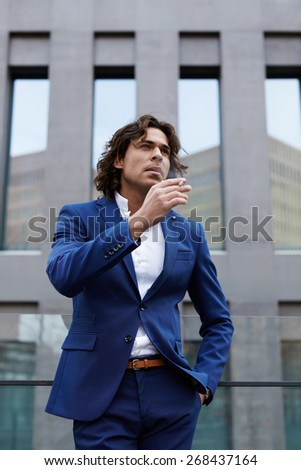 Portrait of handsome young man smoking a cigarette looking concerned and worried - stock photo