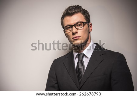 Portrait of handsome young man wearing glasses and suit. Isolated on grey background. - stock photo
