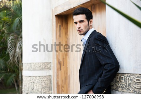 portrait of handsome young man with attitude, young male fasion model wearing winter's attire - stock photo
