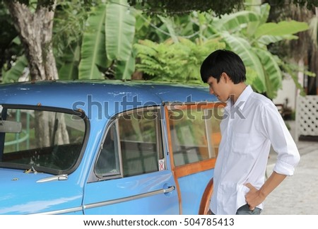 Portrait of handsome young man with car classic