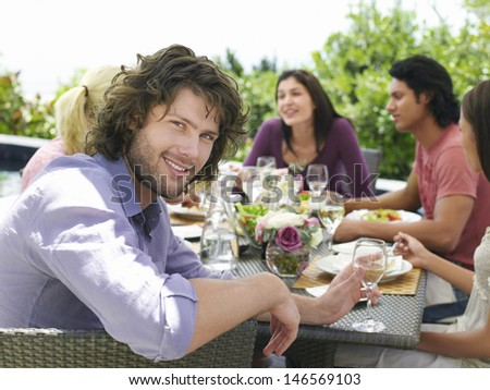 Portrait of handsome young man with friends having meal outdoors