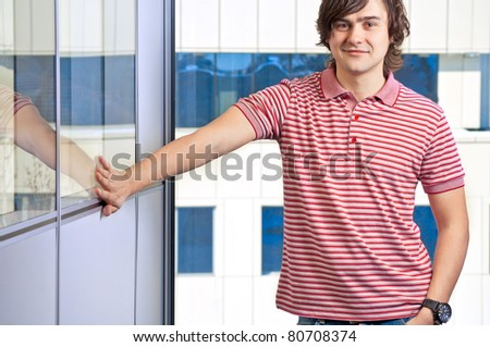 Portrait of handsome young man with the window in the background - stock photo