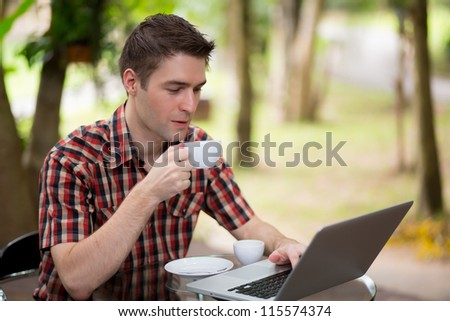 Portrait of handsome young man working with laptop - stock photo