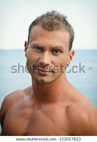 Portrait of handsome young muscle man smiling, outdoors, showing muscular pecs