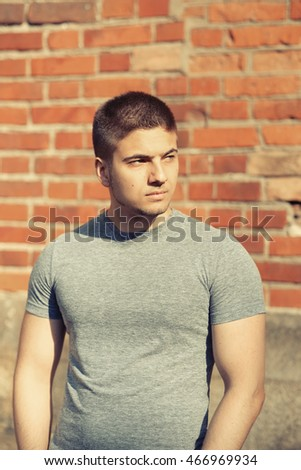 Portrait of handsome young muscular man in front of brick wall