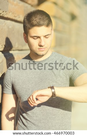 Portrait of handsome young muscular man looking on his wrist watch in urban context