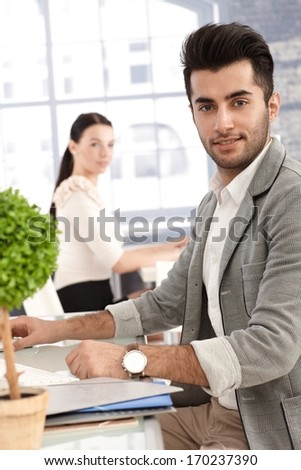 Portrait of handsome young office worker sitting at desk, smiling, female colleague watching in the background.