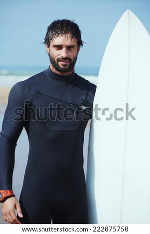 Portrait of handsome young surfer man standing with surfboard against the ocean, young beautiful surfer man in black diving suit holding his surfboard standing on the beach, filtered image - stock photo