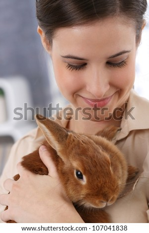 Portrait of happily smiling woman holding cute pet rabbit. - stock photo