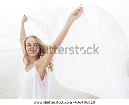 portrait of happiness of beautiful woman with white scarf on the beach