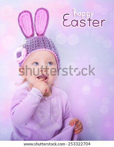 Portrait of happy adorable child wearing cute knitted hat with rabbit ears on pink blur background, greeting card with text space, happy Easter bunny costume - stock photo