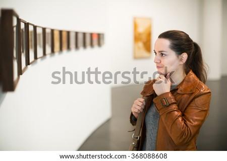 Portrait of happy adult brunette girl in art museum - stock photo
