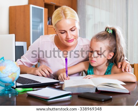 Portrait of happy adult woman and child having lesson indoors  - stock photo