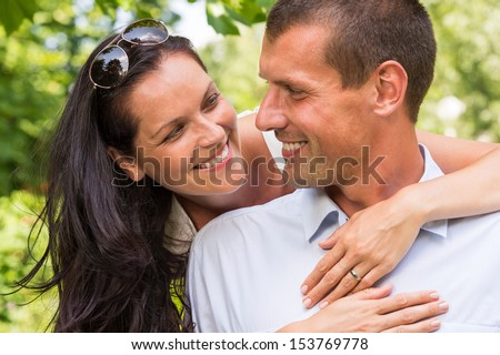 Portrait of happy affectionate couple hugging in park