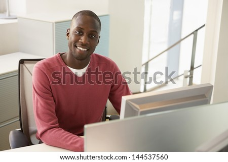 Portrait of happy African American businessman sitting at computer desk - stock photo