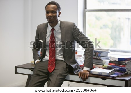 Portrait of happy African American businessman sitting on office desk - stock photo