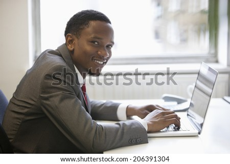 Portrait of happy African American businessman using laptop at office desk - stock photo