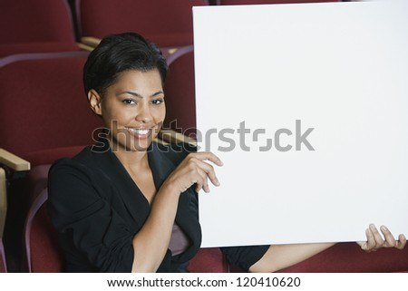 Portrait of happy African American businesswoman holding blank placard while sitting in auditorium