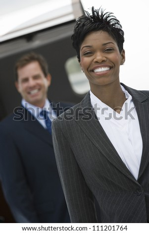 Portrait of happy African American businesswoman with colleague in the background at airfield - stock photo
