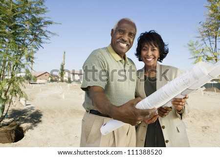 Portrait of happy African American couple holding blueprint - stock photo