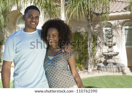 Portrait of happy African American couple standing together near house