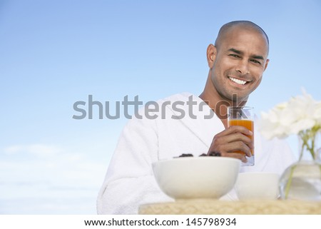 Portrait of happy African American man in bathrobe holding glass of juice outdoors - stock photo