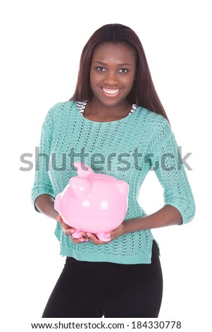 Portrait of happy African American woman holding piggybank against white background