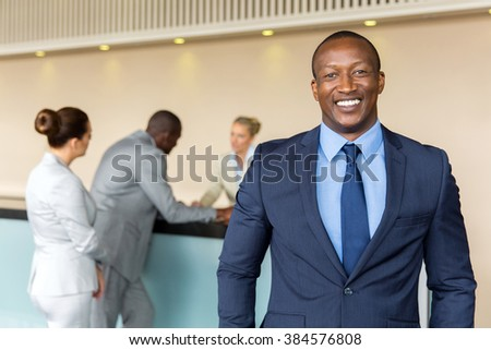 portrait of happy african businessman standing at hotel reception - stock photo