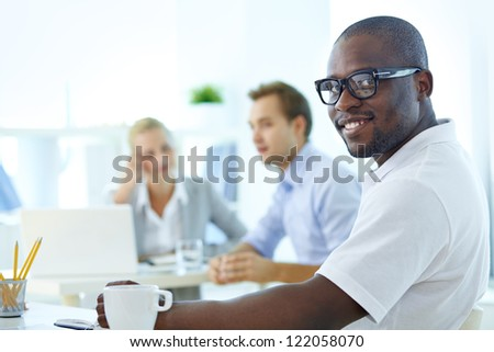 Portrait of happy African guy looking at camera in working environment - stock photo
