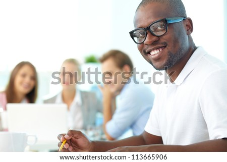 Portrait of happy African guy looking at camera with group of students behind