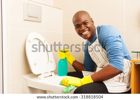 portrait of happy african man cleaning toilet - stock photo