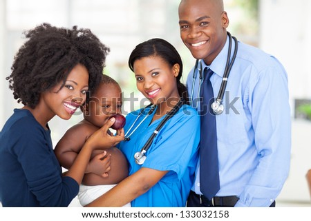 portrait of happy african pediatricians with mother and baby after checkup - stock photo