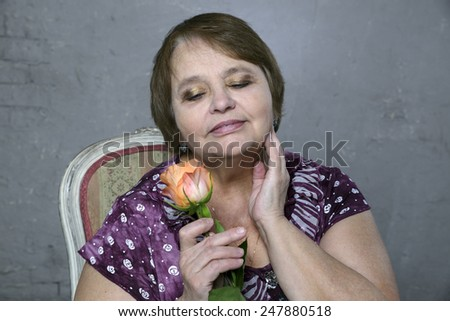Portrait of happy aged woman with orange rose