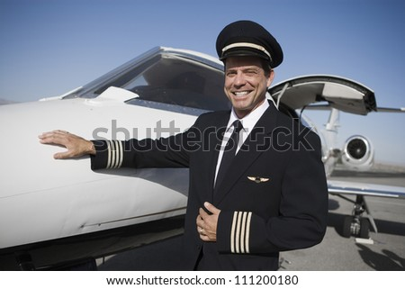 Portrait of happy airplane captain standing by aircraft at airfield - stock photo