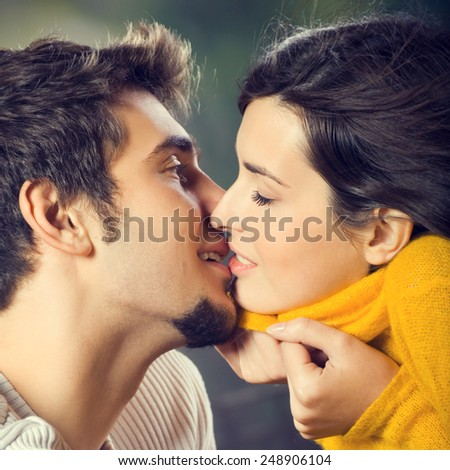 Portrait of happy amorous young couple kissing, outdoor - stock photo