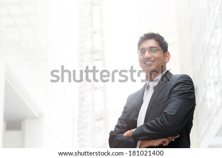 Portrait of happy and confident 30s Asian Indian businessman smiling. India male business man, real modern office building as background. - stock photo