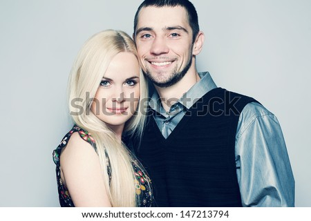 Portrait of happy and loving married couple posing together over light blue background. Casual urban style. Close up. Copy-space. Studio shot - stock photo