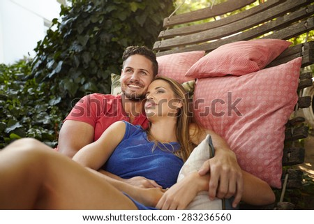 Portrait of happy and peaceful young couple relaxing on hammock in backyard. Man smiling with woman looking away. - stock photo