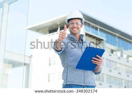 Portrait of happy architect with clipboard gesturing thumbs up outside building - stock photo