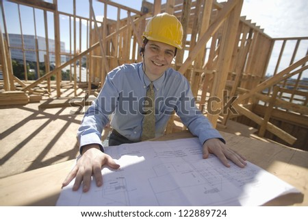 Portrait of happy architect working on blueprint outdoors