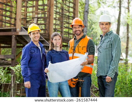 Portrait of happy architects with blueprint standing outside wooden cabin at construction site - stock photo
